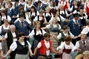 Women and men in traditional costumes dance during the folk dance festival at the Unspunnen festival in Interlaken